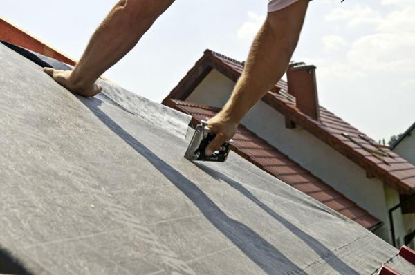 Wykonanie dachu rozpoczyna się od ułożenia folii na drewnianej konstrukcji. Folię zazwyczaj przypina się do więźby takerem.