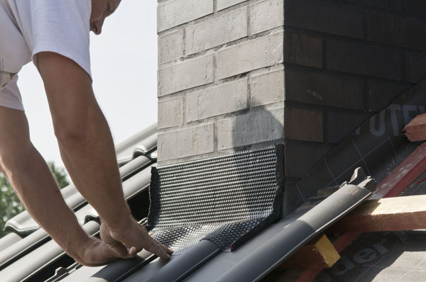 Taśmę do tzw. miękkiej obróbki komina należy nakleić tak, by mocno zachodziła na dachówki i dobrze docisnąć do powierzchni pokrycia.